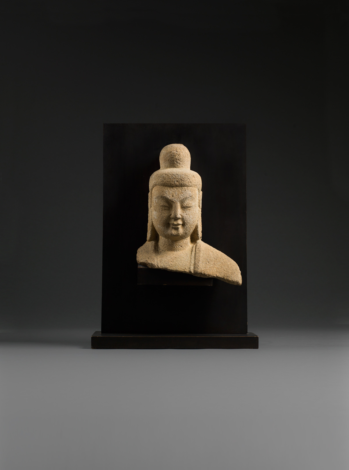 Sandstone head and shoulders of Buddha